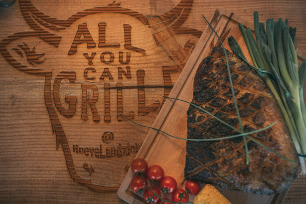 Restaurant All you can grill logo in hout gegraveerd met bavette steak op plank